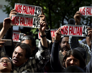 Family members of the 43 students display signs during the GIEI's presentation of their findings on Sunday. Source: The New York Times.