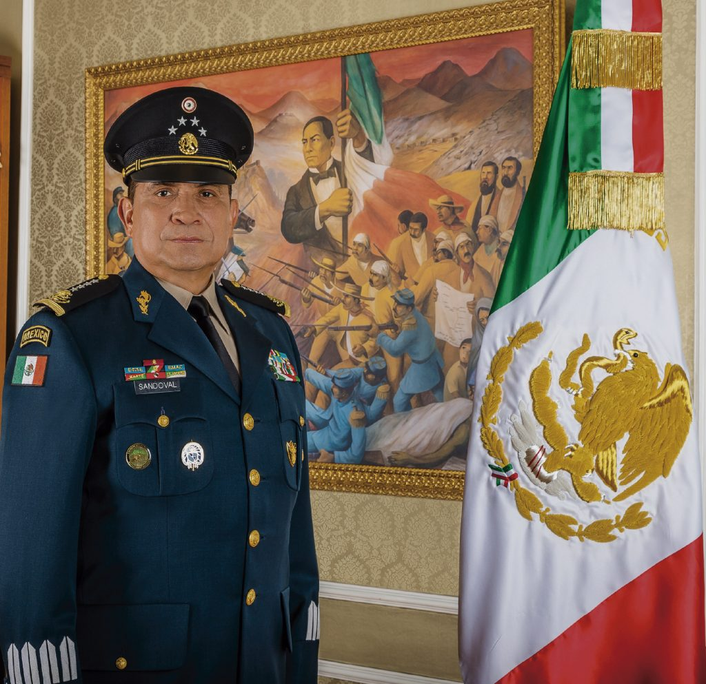 SEDENA's director, General Sandoval González, stands in front of a historic painting and the Mexican flag.